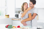 Wife jokingly feeding husband in kitchen — Stock Photo