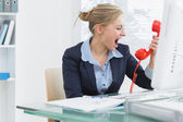 Female executive yelling into red telephone receiver at desk — Stockfoto