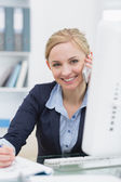 Portrait of business woman writing while on call at office — Stock Photo