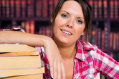 Girl leaning on books with a smile — Stock Photo