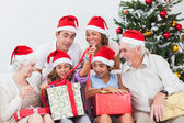 Family watching little girl opening christmas present — Stock Photo