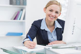 Smiling business woman writing notes at office desk — Stock Photo