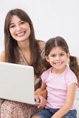 Mother and daughter happily using laptop — Stock Photo
