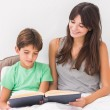 Stock Photo: Mother and son reading in bed