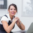 Smiling female executive sitting with laptop at desk — Stock Photo