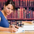 Foto Stock: Cute girl writing on notebook in library