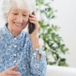 Elderly happy woman calling someone — Stock Photo