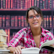 Female college student sitting with books at library — Stock Photo