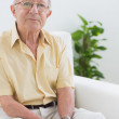 Elderly man sitting on the sofa — Stock Photo #24110331