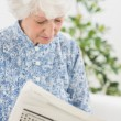 Stock Photo: Elderly focused womreading newspapers