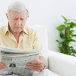 Stock Photo: Elderly serious mreading newspapers