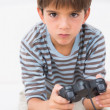 Stockfoto: Boy playing his game console