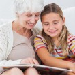 Little girl reading with granny - Stock Photo