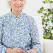 Aged woman sitting on sofa — Stock Photo