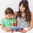 Stock Photo: Mother and son using tablet pc