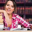 Woman leaning on books with a smile — Stock Photo
