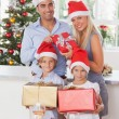 Family holding christmas presents — Stock Photo