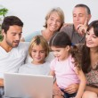 Happy family looking at laptop — Stock Photo