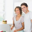 Smiling wife chopping vegetables with husband — Stock Photo