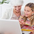 Granny and little girl using laptop — Stock Photo