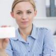 Female executive holding blank card at office — Stock Photo