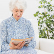 Elderly woman reading a old book — Stock Photo