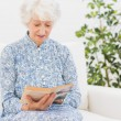 Stock Photo: Elderly womreading old book
