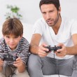Father and son playing video games - Stock Photo