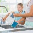 Daughter helping mother do the washing up — Stock Photo #24111723