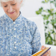 Stock Photo: Elderly womlooking at her album