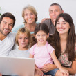 Happy family on couch using laptop - Stock Photo