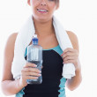 Portrait of woman in sportswear holding towel around neck and wa — Stock Photo #24111977
