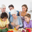 Family watching grandmother slicing pepper — Stock Photo