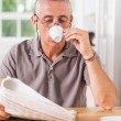 Stock Photo: Mreading newspaper and drinking espresso