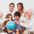 Extended family looking at globe — Stock Photo