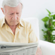 Stock Photo: Elderly focused mreading newspapers