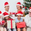 Stock Photo: Excited family exchanging gifts at christmas