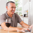 Happy man using laptop with glass of red wine - Foto Stock