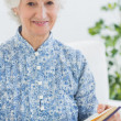 Stock Photo: Elderly smiling womwith photo album