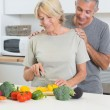Couple cutting vegetables together — Stock Photo #24112581