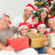 Happy family at christmas holding gifts — Stock Photo #24112813