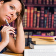 Stock Photo: Cute woman thinking with pen and book