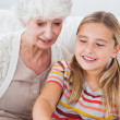 Little girl and granny using laptop — Stock Photo