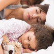 Stock Photo: Mother and children cuddled up in bed