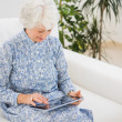 Elderly cheerful woman using a digital tablet — Foto Stock