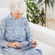 Stock Photo: Elderly cheerful womusing digital tablet