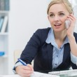 Business woman writing while on call at office — Stock Photo
