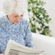 Stock Photo: Elderly cheerful womreading newspapers