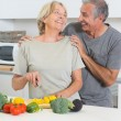 Smiling couple cutting vegetables together — Stock Photo