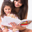 Mother and daughter reading a storybook - Stock Photo